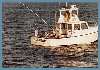 Several men in saltwater fishing apparel on a fishing rig boat named fishtrap